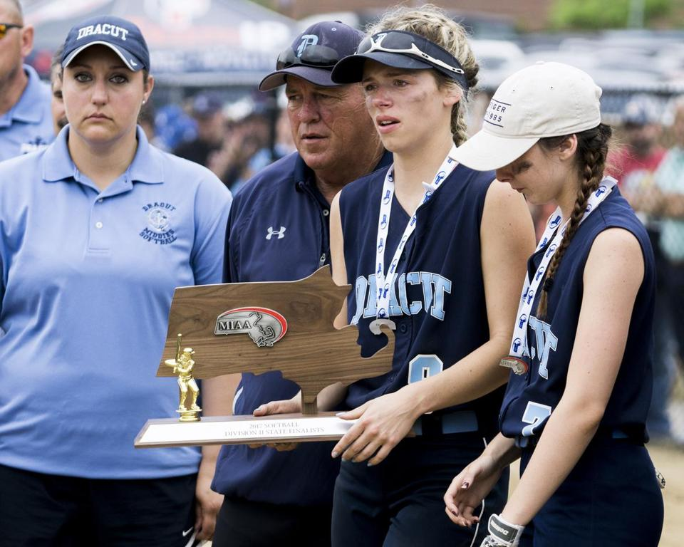 There was no consolation in holding the runner-up trophy for Dracut captain Michelle Gaudreau (second from right) as she stood flanked to her right by head coach George Roy during the postgame award ceremony.