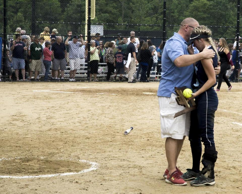 8.3.2827582534_Sports_18hssoftball Dracut captain Michelle Gaudreau (9) holds the second place trophy as she is comforted by an assistant coach following their loss 10-1 to Grafton at the Div. 2 State Softball Final in Worcester State College in Worcester, Mass., Saturday, June 17, 2017. (Robert E. Klein for the Boston Globe)