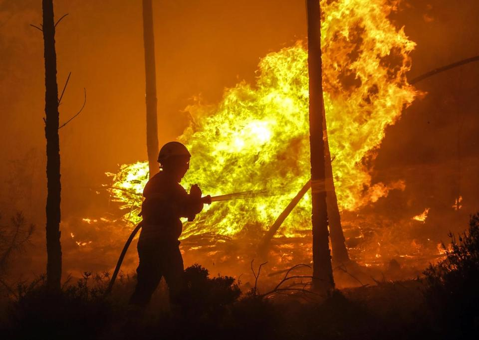 epa06035918 A Firefighter battles with a fire in Pampilhosa da Serra, central of Portugal, 18 June 2017. At least sixty two people have been killed in forest fires in central Portugal, with many being trapped in their cars as flames swept over a road on the evening of 17 June 2017. A total of 733 firefighters are providing assistance. EPA/PAULO NOVAIS