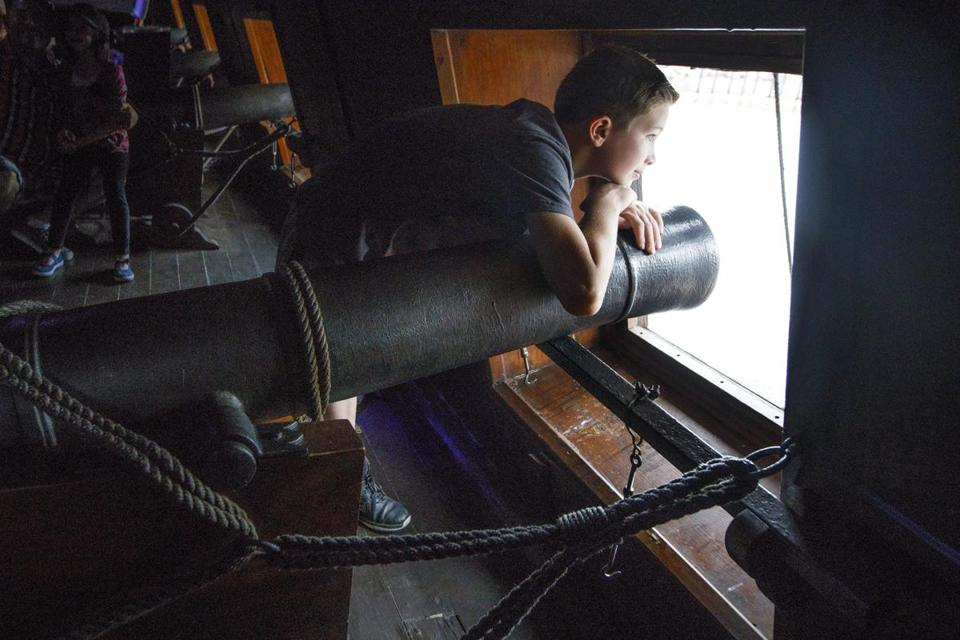 Boston, MA - 6/18/2017 - Owen Guelcher, 9, looks out of one of the cannon window of the tall ship El Galeon of Spain as he takes the public tours of tall ships as part of the Sail Boston event on Fan Pier in Boston, MA, June 18, 2017. (Keith Bedford/Globe Staff)