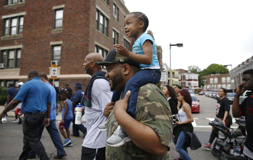 Boston, MA -- 6/18/2017 - Akeem Jackson (C) carries his daughter Aubrey, 3, on his shoulders during the Father's Day Unity Walk. (Jessica Rinaldi/Globe Staff) Topic: 19fathers Reporter: