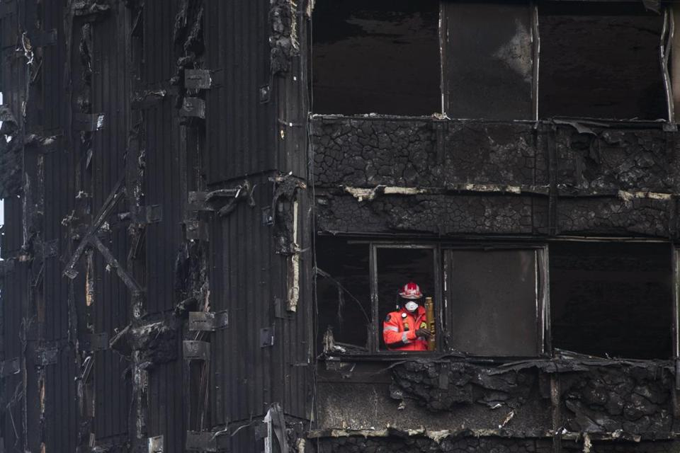 A fireman looked out Sunday from the remains of London's Grenfell Tower.