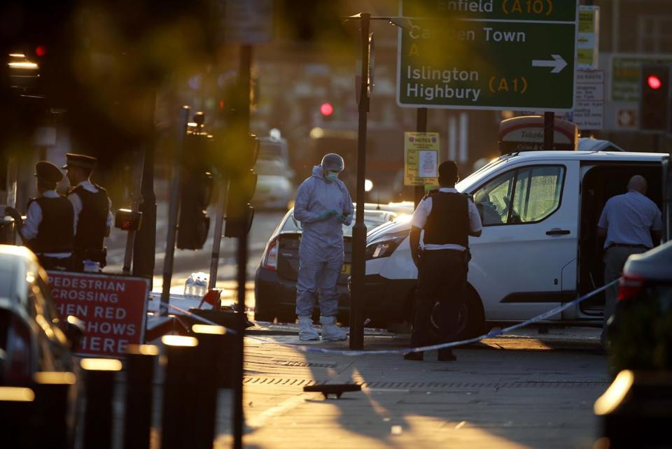 Forensic experts stood next to the van suspected of running down people on Monday in Finsbury Park, London.