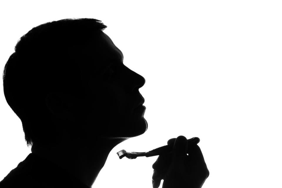 Young man shaving in the morning - silhouette