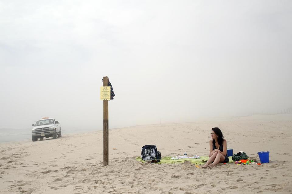 A woman sat on the border of Island Beach State Park as a park ranger patrolled the coastline on Saturday.