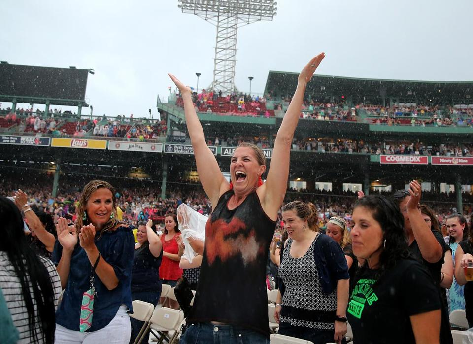 A fan in the pouring rain enjoyed herself during Paula Abdul's performance.