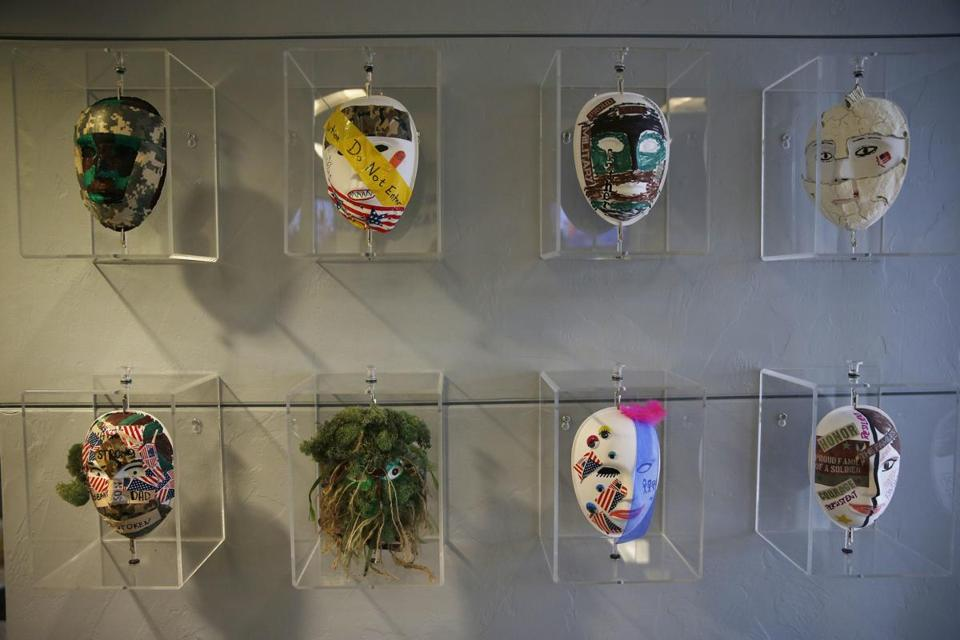 Masks made by patients during an art therapy session hangs on the wall at the Home Base clinic.