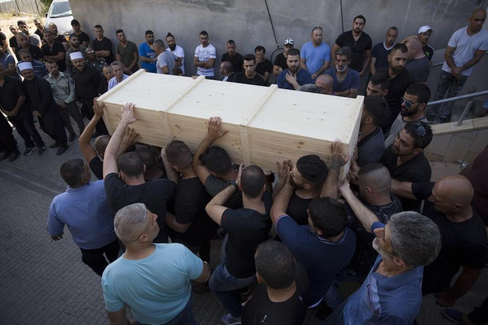 Druze men carry the coffin of Israeli police officer Advanced Staff Sgt. Maj. Hael Sathawi in Mughar, Israel, Friday, July 14, 2017. Arab assailants struck at ground zero of the Israeli-Palestinian conflict on Friday opening fire from inside a major Jerusalem shrine and killing two Israeli policemen. The two slain policemen were members of Israel's Druze community, followers of a secretive off-shoot of Islam. (AP Photo/Ariel Schalit)