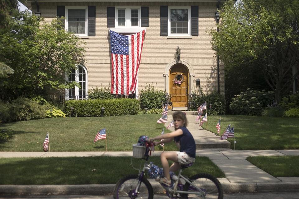 A girl pedals past a house decorated with American flags during the annual Sauganash Fourth of July Parade and Picnic, Tuesday, July 4, 2017, in the Sauganash neighborhood of Chicago. (Alyssa Pointer/Chicago Tribune via AP)