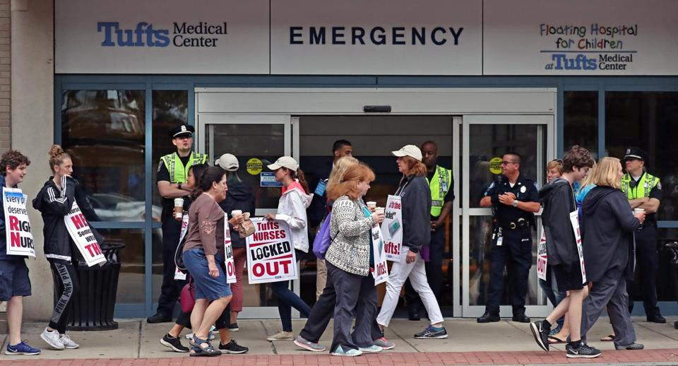 Tufts Medical nurses in a picket line by the doors of the medical center in Chinatown.