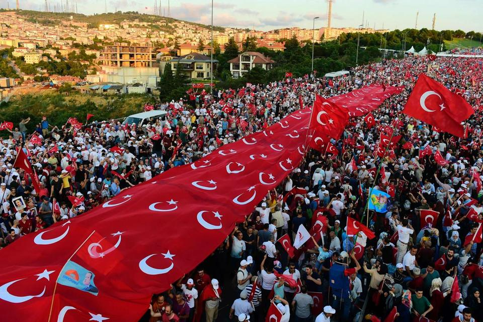 People stood under Turkish flags as they gathered on the Martyrs' Bridge in Istanbul.