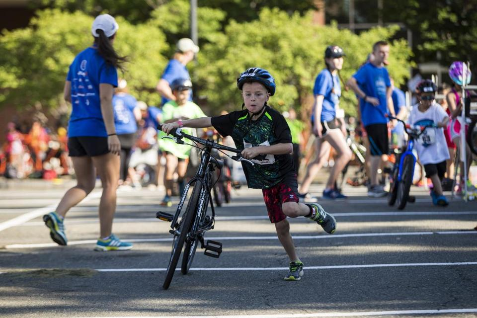 A boy hustled during the biking portion of the New England Kids Triathlon in Cambridge on Sunday.