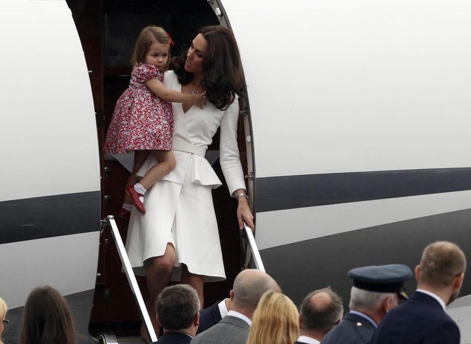 Britain's Kate, the Duchess of Cambridge held Princess Charlotte as they arrive at the airport.