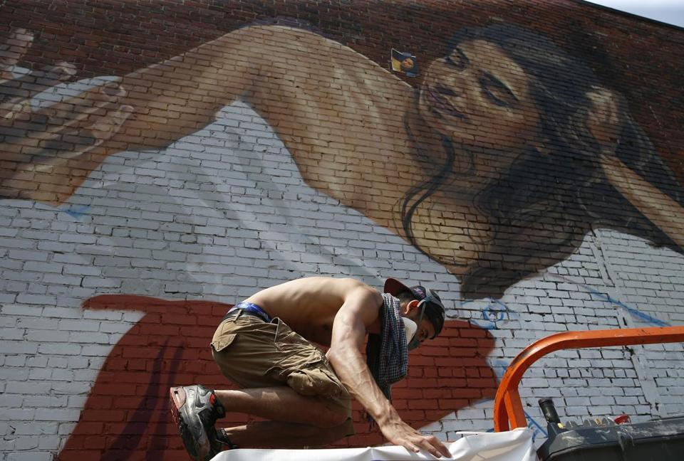 Lynn, MA -- 7/18/2017 - Montreal based artist, FONKi, (cq) climbs up on a cherrypicker to work on his mural as he takes part in the mural festival, where 10 murals are underway by international and local artists as part of Beyond Walls. (Jessica Rinaldi/Globe Staff) Topic: 20lynnmuralpic Reporter: