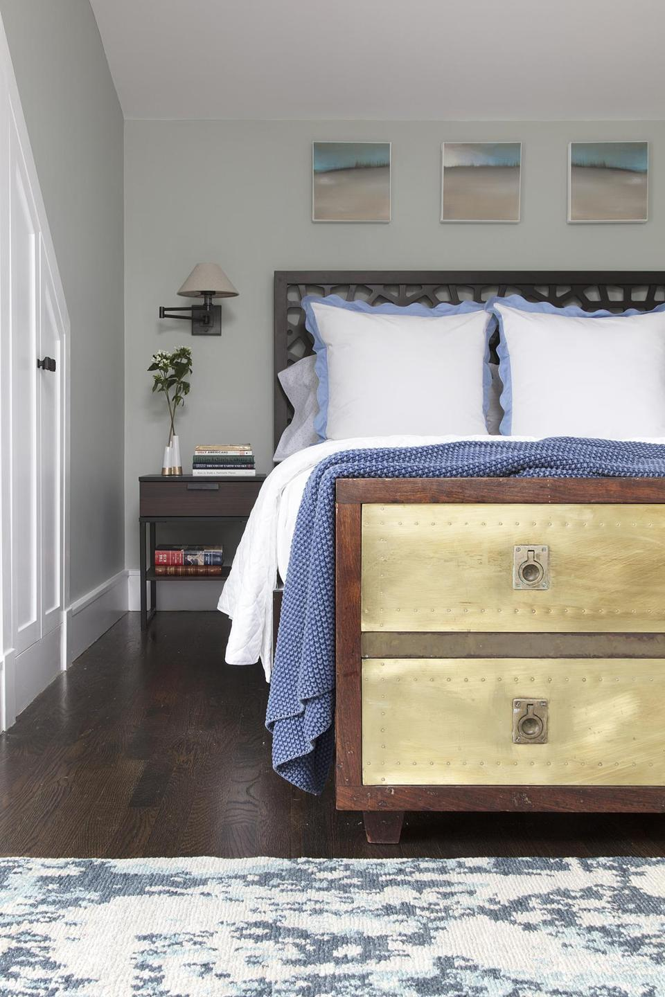 "For the master bedroom, Scales chose a West Elm ""Morocco"" headboard in chocolate. Swing-arm sconces with linen shades are from Restoration Hardware. At the foot of the bed is Jim's mother's hope chest, made by his dad."