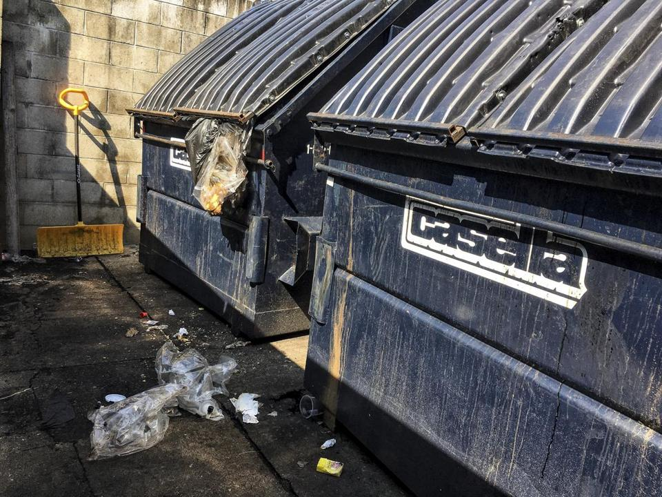 A ripped bag of trash hung out of a poorly secured dumpster behind Dunkin Donuts in Lincoln, N.H.