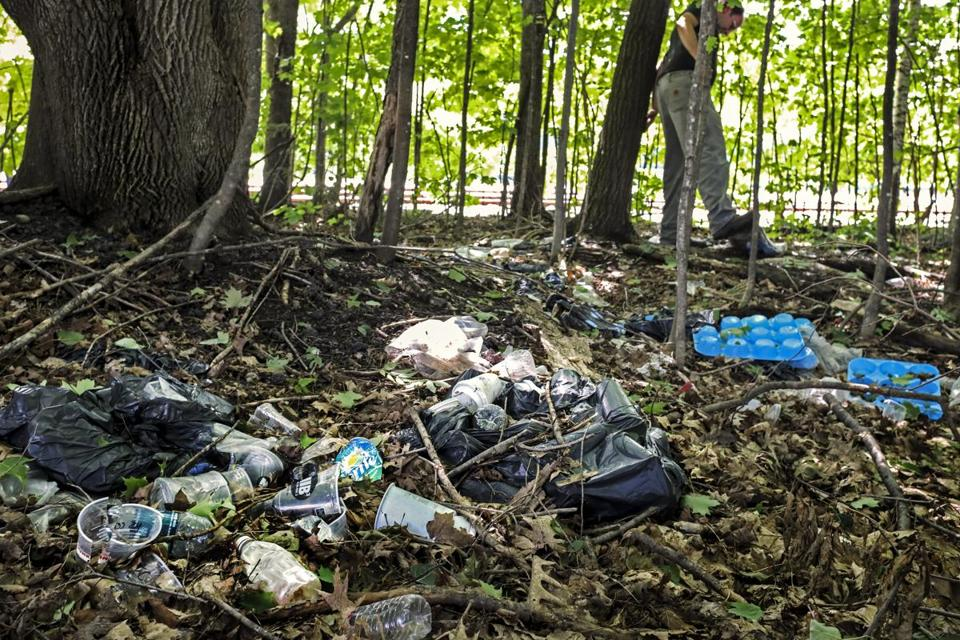 Many years' worth of trash was strewn in a wooded strip between a walking trail and local businesses in Lincoln.