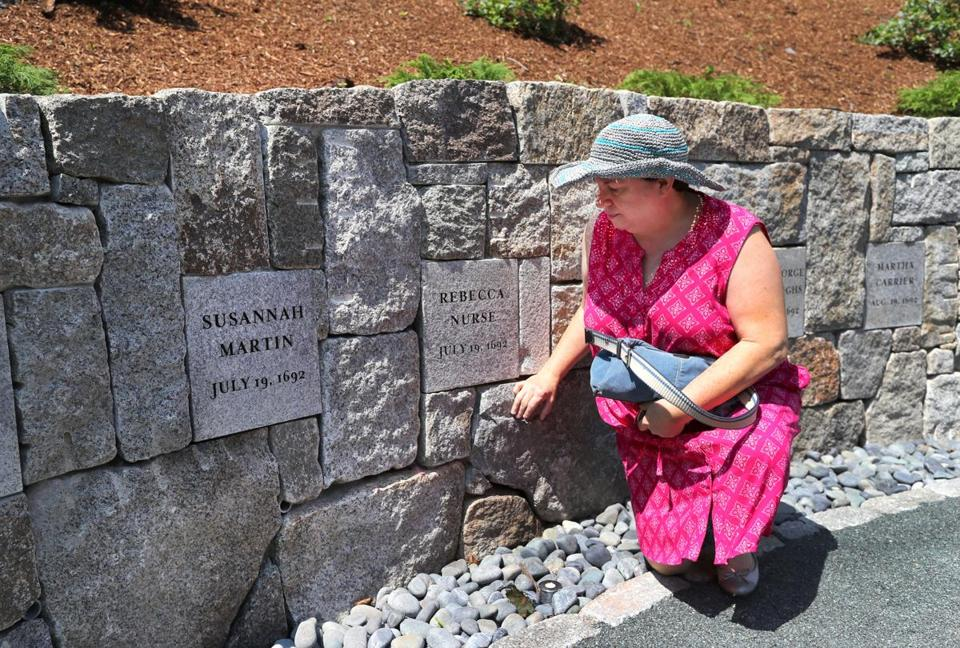 Benita Towle from Milford, Conn., stooped to touch the stone of executed witch, Rebecca Nurse, who was hanged on July 19, 1692. She is the seventh great-granddaughter of Nurse.