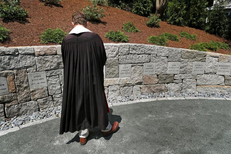 The Rev. Jeffrey Barz-Snell looked at the witches names on the wall before the dedication of the new Proctor's Ledge Memorial.