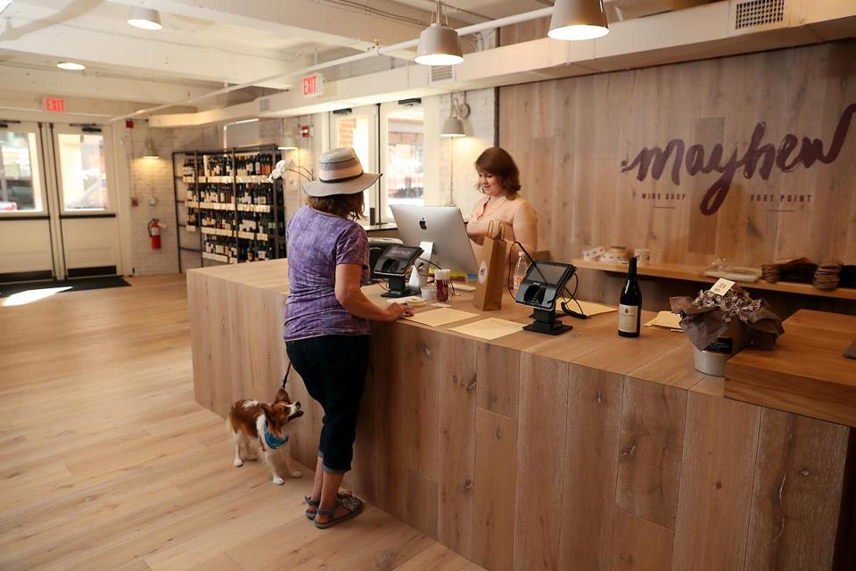 South Boston MA 07/22/17 Chadler Parker (cq) selling a bottle of wine to Joann Dunlavey (cq) and her dog, Bentley at Mayhew a retail wine shop in the Fort Point neighborhood is located across the street from the New Amazon Headquarters. (Matthew J. Lee/Globe staff) topic: reporter:
