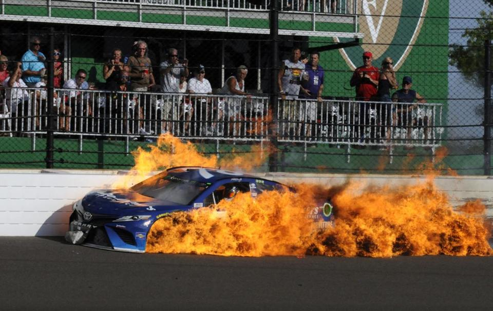 The car driven by Martin Truex Jr. burns after a crash with Kyle Busch during the NASCAR Brickyard 400 auto race at Indianapolis Motor Speedway in Indianapolis, Sunday, July 23, 2017. (AP Photo/Greg Huey)