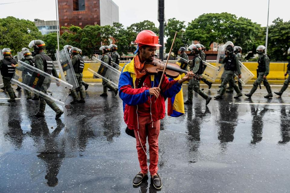 (FILES) This file photo taken on May 24, 2017 shows opposition activist and violin player Wuilly Arteaga during a protest against President Nicolas Maduro in Caracas. According to a human rights NGO report, Artega, 23, was arrested on July 27, 2017, during a protest within a 48-hour strike called by the opposition. / AFP PHOTO / FEDERICO PARRA