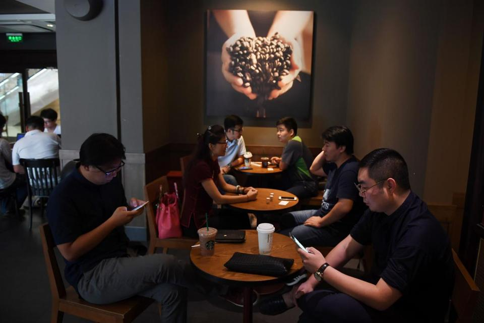 Customers in a Beijing Starbucks. Starbucks Corp. last month extended its reach in China with a $1.2 billion deal for control of more than 1,000 coffee shops.