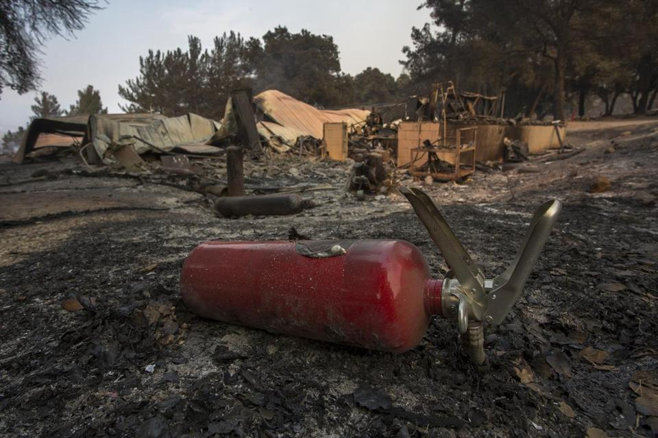 SANTA BARBARA, CA - JULY 09: A burned fire extinguisher is seen next to structures at Rancho Alegre Boy Scouts of America outdoor school that were destroyed by the Whittier Fire on July 9, 2017 near Santa Barbara, California. The Whittier Fire and the Alamo Fire together have blackened more than 30,000 acres of chaparral-covered hills in Ventura County. Statewide, about 5,000 firefighters are fighting 14 large wildfires. (Photo by David McNew/Getty Images)