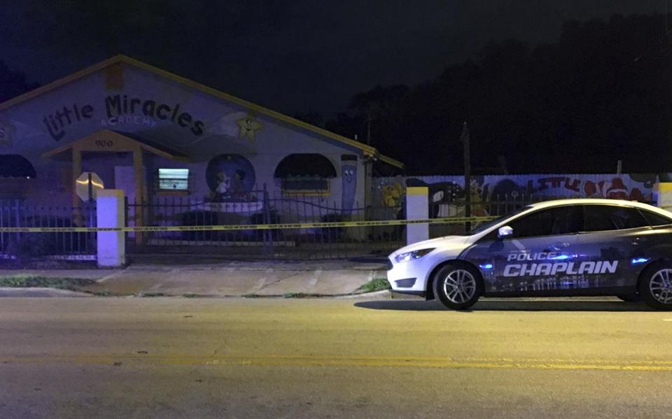 An Orlando Police chaplain car is parked in front of a day care center in Orlando, Fla., where a young boy was found dead after being left in a van.
