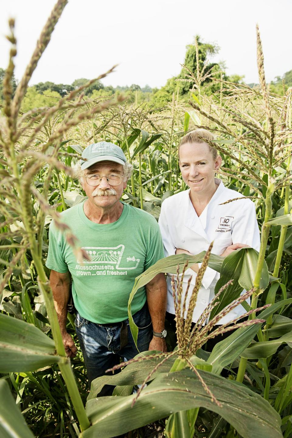 "Charles ""Chip"" Poutasse  of Brigham Farm Stand and Carolyn Johnson  of 80 Thoreau, surrounded by sweet corn."