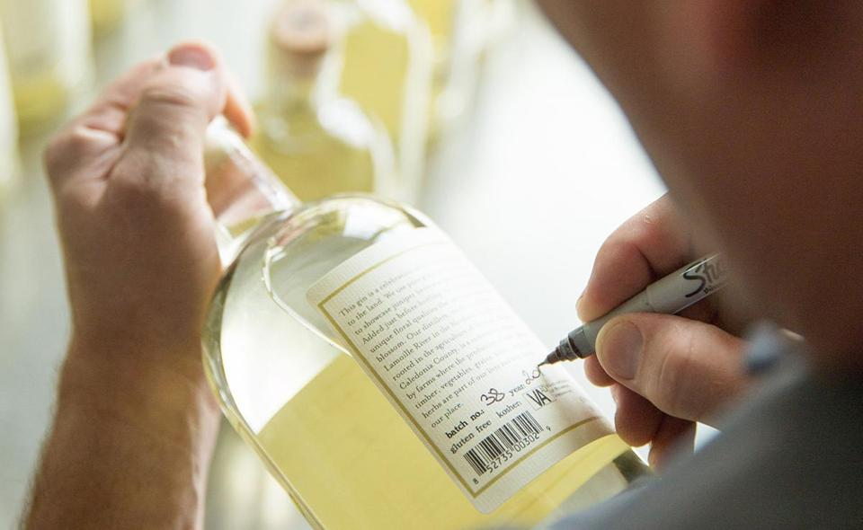 An employee at Caledonia Spirits marks a bottle of Barr Hill gin with the date and batch number.