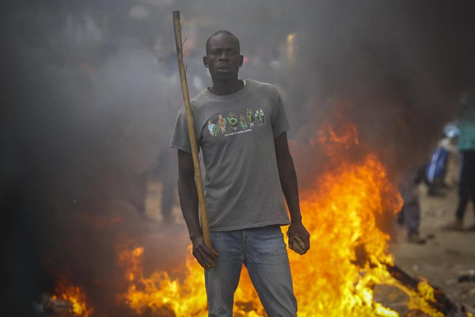 A supporter of opposition leader Raila Odinga stands in front of a burning barricade Saturday in Nairobi.