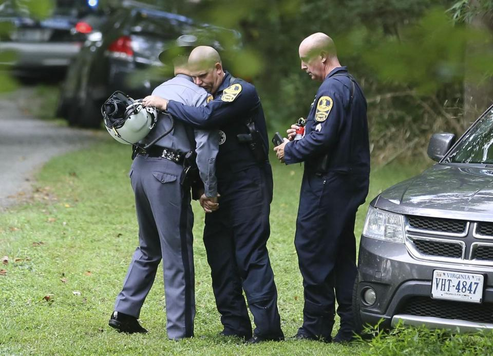 Law enforcement officials embraced near the scene of the deadly helicopter crash.