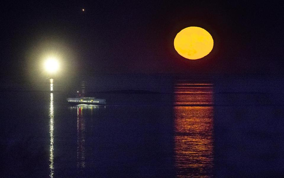 Boston, Ma-November 14 2016- - The Super Moon rises as a ferry from Hingham heads past Boston Light towards downtown Boston.