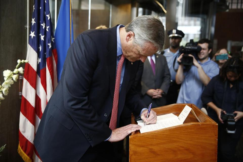 Governor Charlie Baker signed a condolence book for Charlottesville after speaking at a press conference Monday.