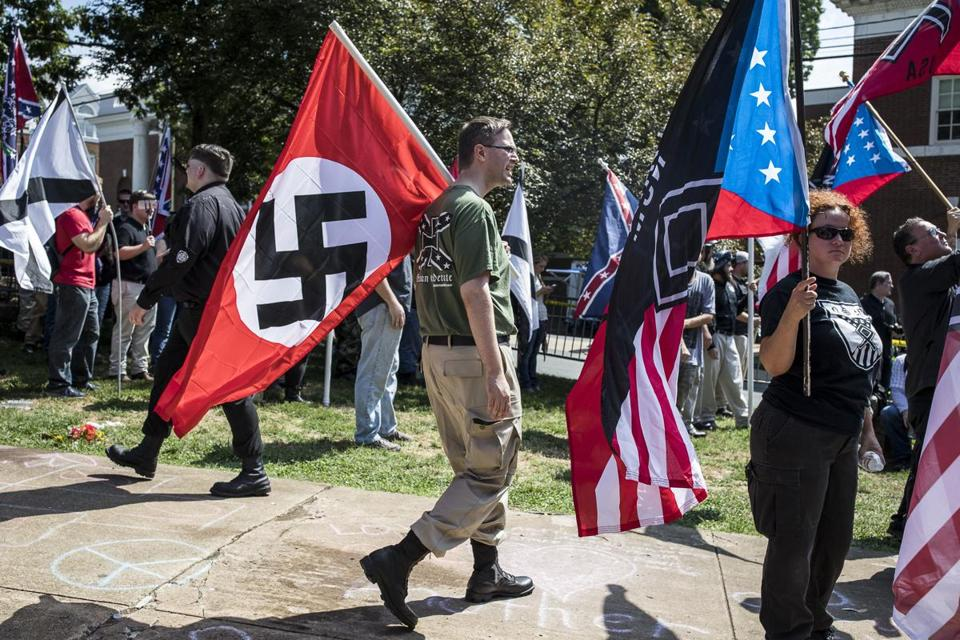 A white nationalist carries a Nazi flag during a protest in Charlottesville, Va., Aug. 12, 2017.