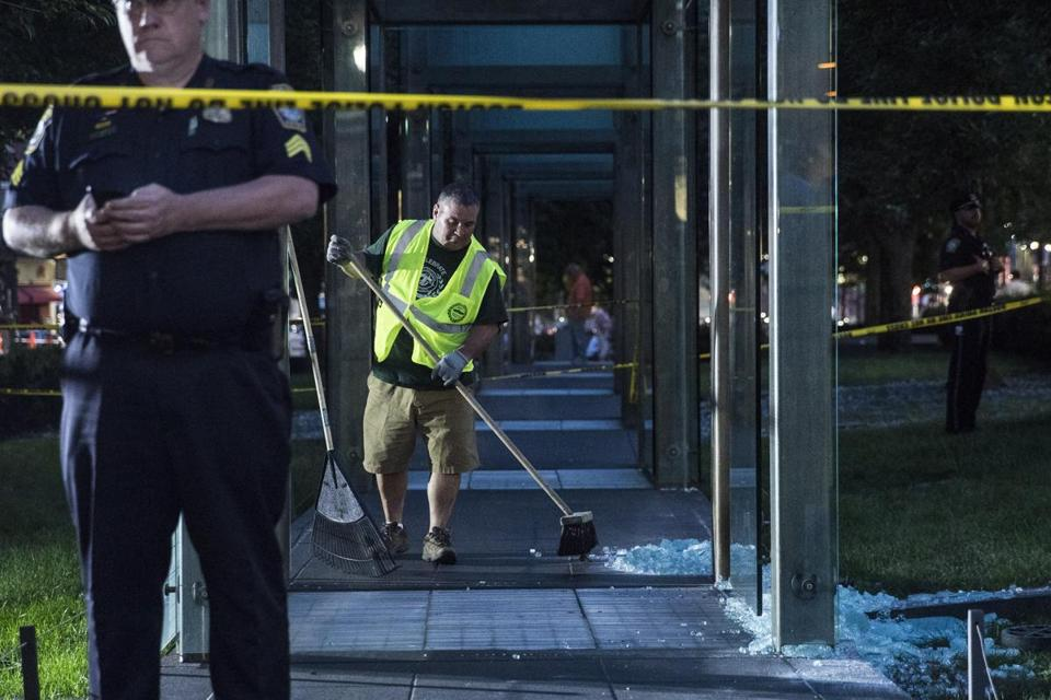 Employees cleaned up the shattered glass at the memorial.