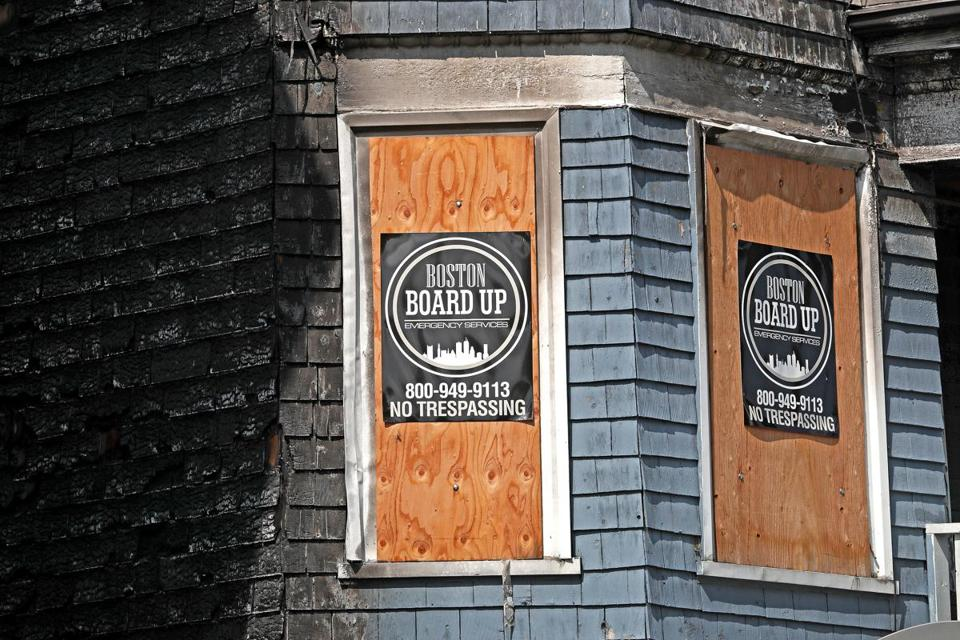 Boarded-up windows at 10 Marie St., which was damaged by a nearby fire.