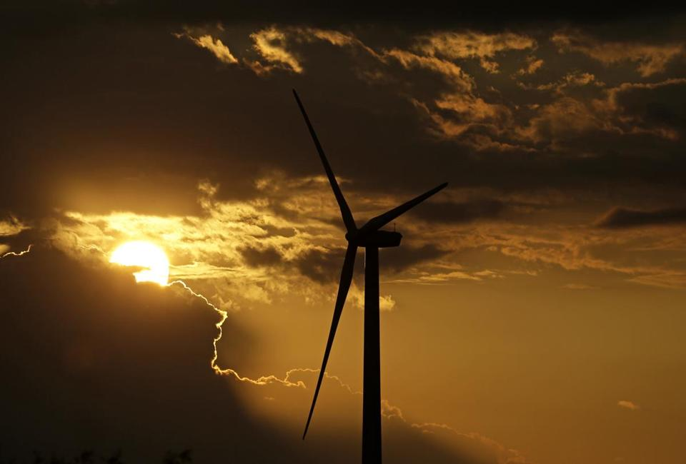 A wind turbine, which is part of the Lost Creek Wind Farm, is silhouetted against the setting sun Thursday, June 1, 2017, near King City, Mo. (AP Photo/Charlie Riedel)