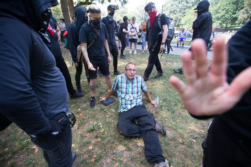 epa06152312 A white nationalist supporter is surrounded by antifascist counter-protesters after he was knocked down by the group on the Boston Common in Boston, Massachusetts, USA, 19 August 2017. Thousands of both white nationalists or the 'Alt-Right' and counter protesters have organized protests in Boston. EPA/MATTHEW HEALEY