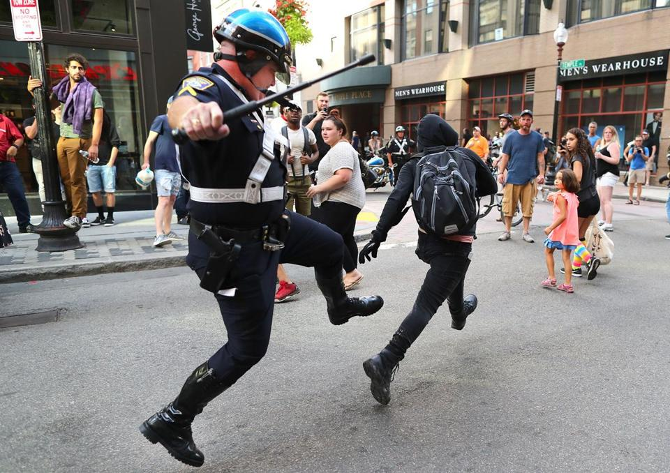 A Boston police officer chased a protester down Washington Street in Downtown Crossing on Saturday.