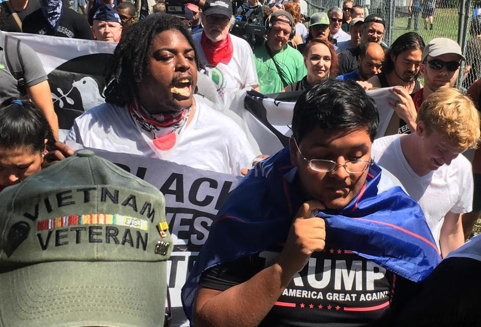 Boston, MA - 08/19/2017 - A pair of Trump supporters are taunted by the crowd as they are escorted into the rally by veterans for peace. (Craig F. Walker/Globe Staff) Reporter: Topic: