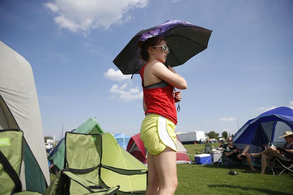 Hopkinsville, KY -- 8/19/2017 - Lauren Boehm, of Pittsburgh grabs some shade under a constellation of stars decorating her umbrella at a makeshift campground in Hopkinsville city nearest the point of greatest eclipse. (Jessica Rinaldi/Globe Staff) Topic: 21EclipseNashville Reporter: Nestor Ramos
