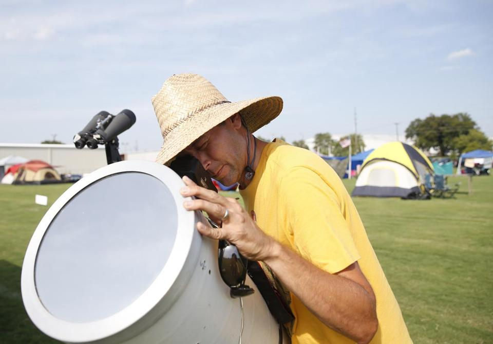 Hopkinsville, KY -- 8/19/2017 - Brian Badgett, of Louisville, positions his camera inside a telescope so that he can photograph tomorrow's eclipse from a makeshift campground in Hopkinsville city nearest the point of greatest eclipse. (Jessica Rinaldi/Globe Staff) Topic: 21EclipseNashville Reporter: Nestor Ramos