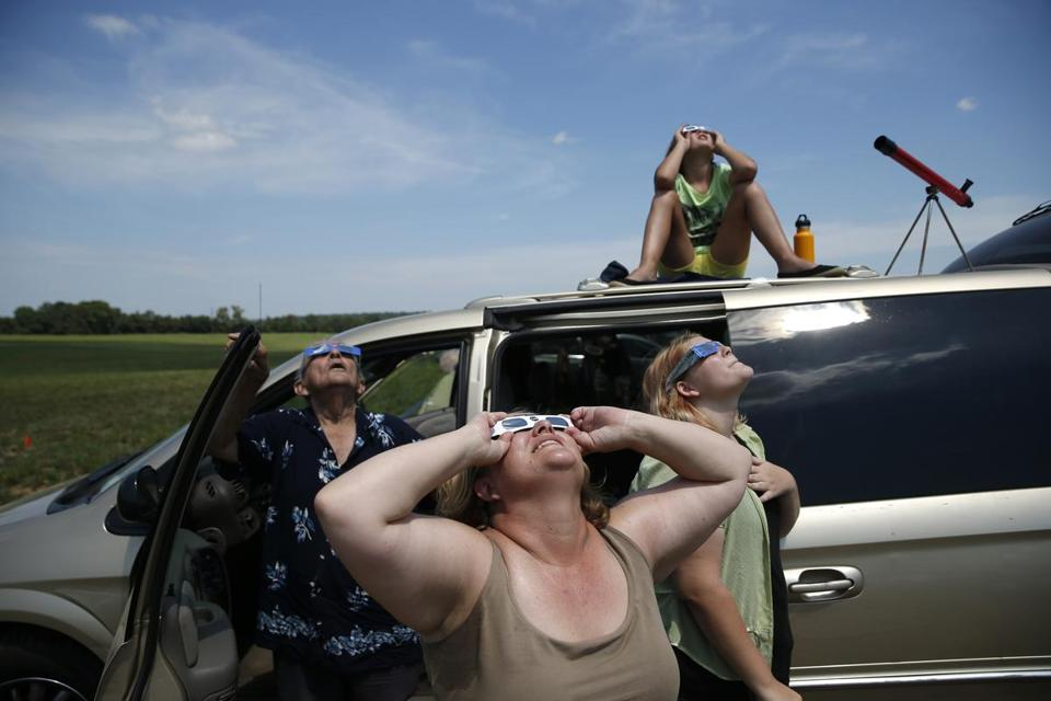 Stephanie Handwerk, center, watched the sky as Terry Queen, left, looked up and Olivia Handwerk, top, watched from the roof of their car as the eclipse takes place in Hopkinsville.