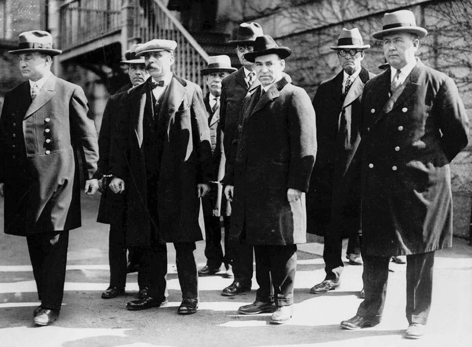 Bartolomeo Vanzetti (second from left foreground) and Nicola Sacco (second from right foreground) stood in handcuffs circa 1927.