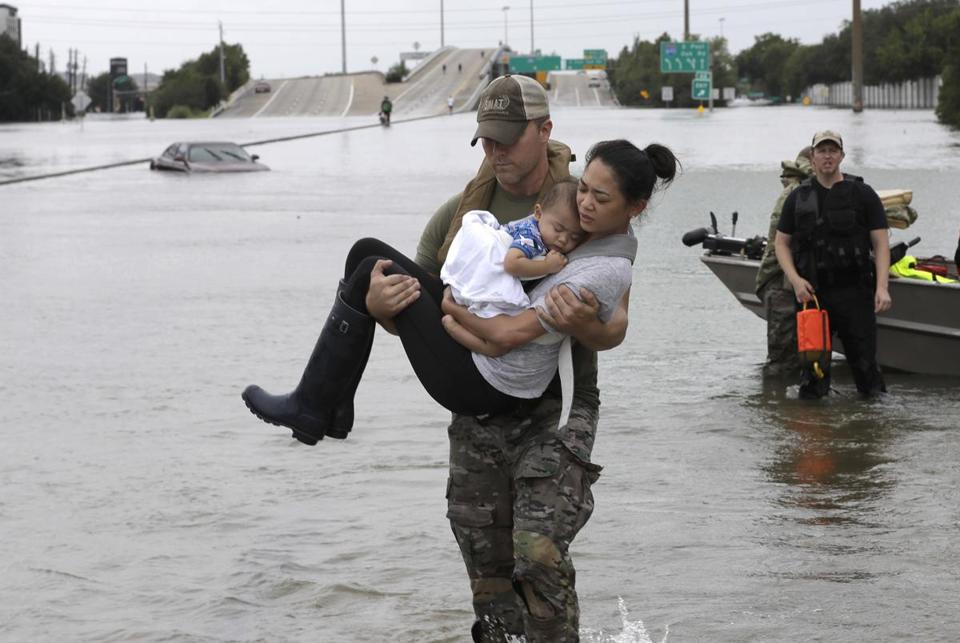 Houston Police SWAT officer Daryl Hudeck carried Catherine Pham and her 13-month-old son Aiden after rescuing them Sunday.