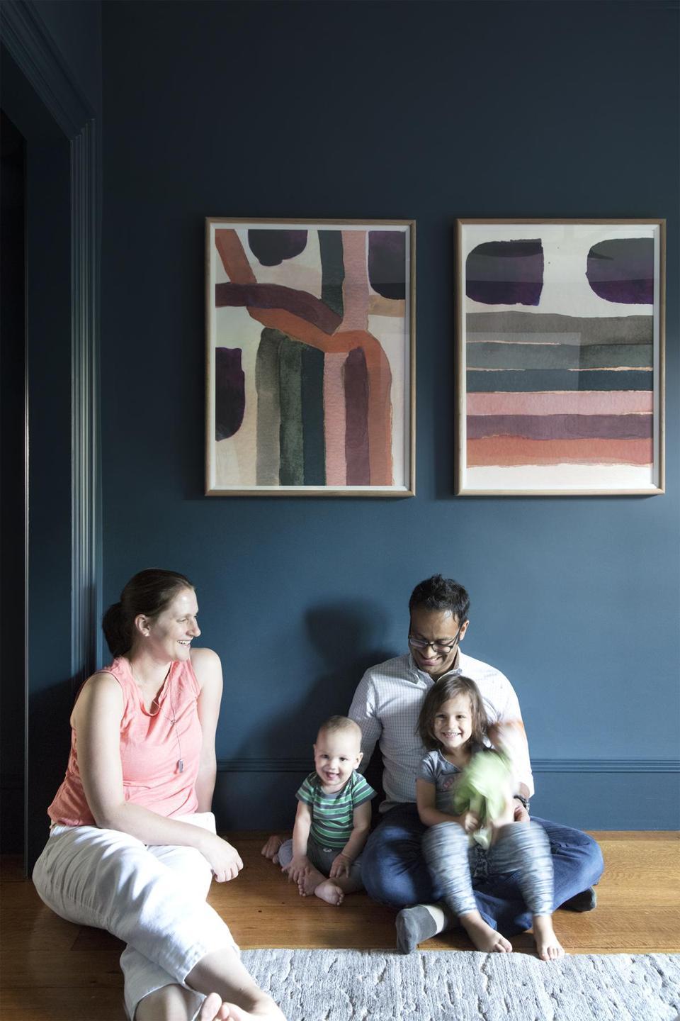 Melissa Spencer, Raj Basu, and their children relax in the master bedroom, where limited-edition abstract prints from Zoe Bios Creative add a pop of color.
