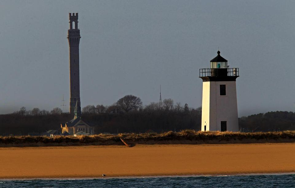 PROVINCETOWN, MA. 03/ 11 /13: A couple of towers, the Pilgrim Monument left and the Long Point Lighthouse right on the shoreline off Provincetown at dusk entering into the evening. ( David L Ryan/Globe Staff Photo ) SECTION: METRO TOPIC stand alone photo