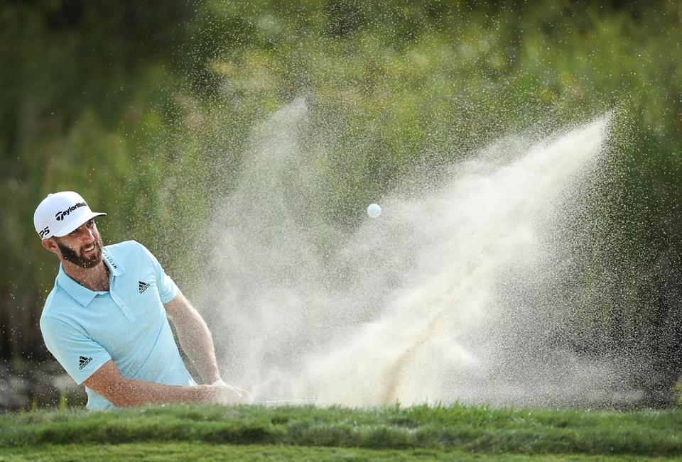 Hitting out of a sand trap on No. 10, it was a long day for first-round leader Dustin Johnson.